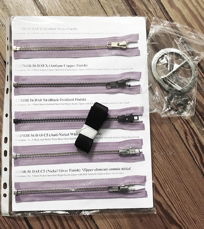 YKK zippers, black ribbon, O shape buckle.