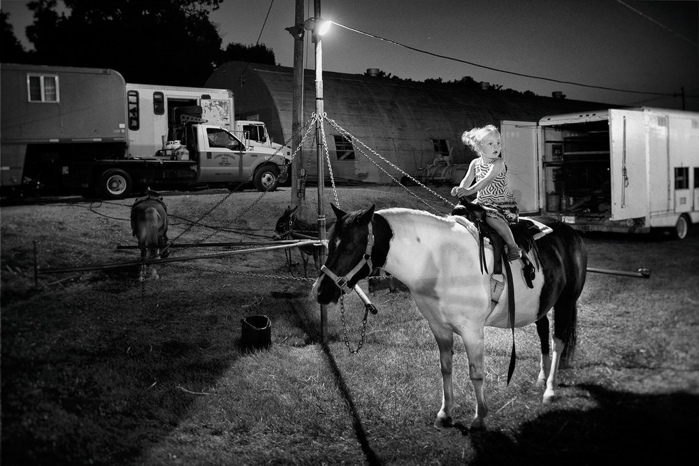 Child on a pony outside the tent in Brooklyn, Iowa.