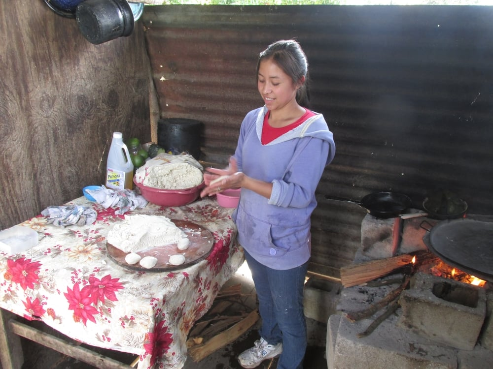 Maritza shows up how to clap the corn meal into round, thin tortillas that are put on the fire to cook.