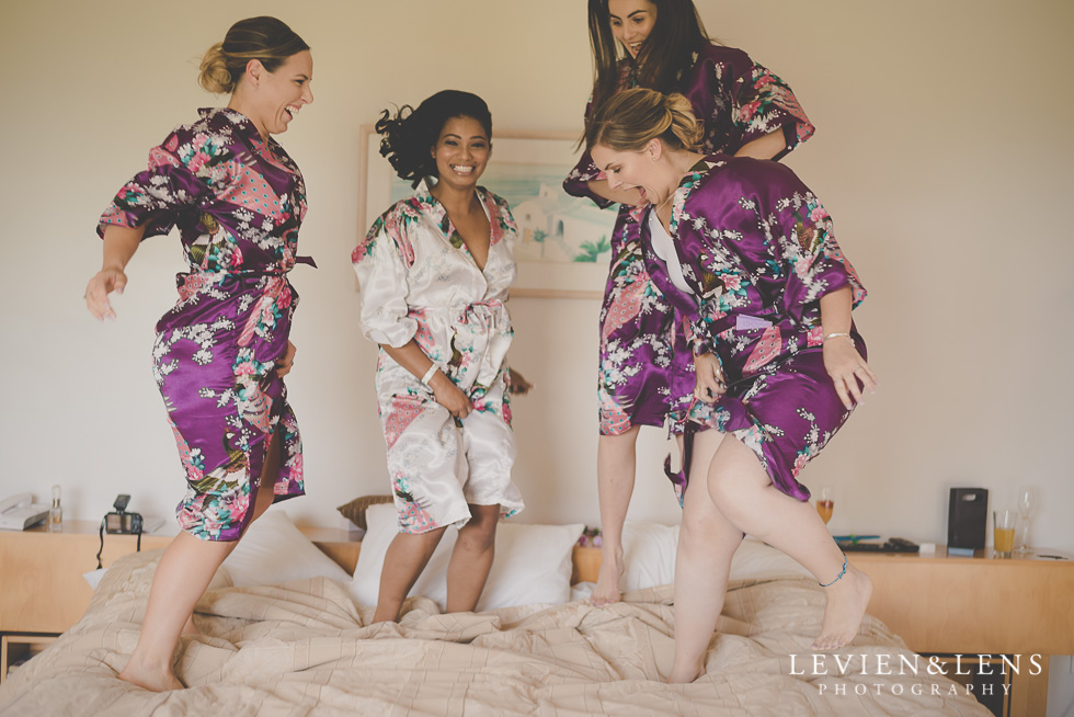 bride with bridesmaids jumping on bed {Auckland-Waikato wedding photographer}