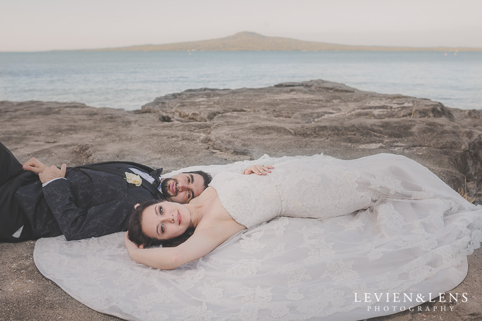 bride groom laying cliff St Heliers beach {Auckland-Hamilton-Tauranga wedding photographer}