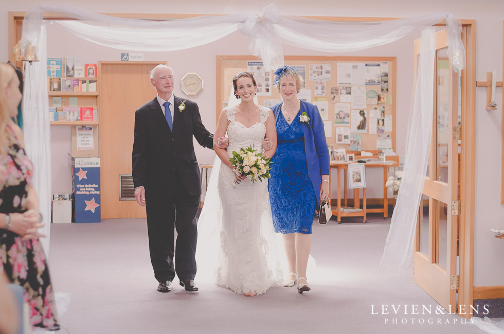 bride with mum dad walking down aisle ceremony St Anthony's Catholic Church Waiuku {Auckland wedding-couples-engagement photographer