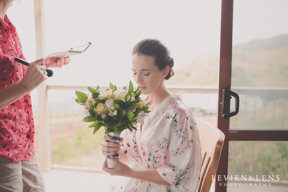 bride smell flowers Castaways Resort - Kariotahi beach wedding {Auckland lifestyle couples-engagement photographer}