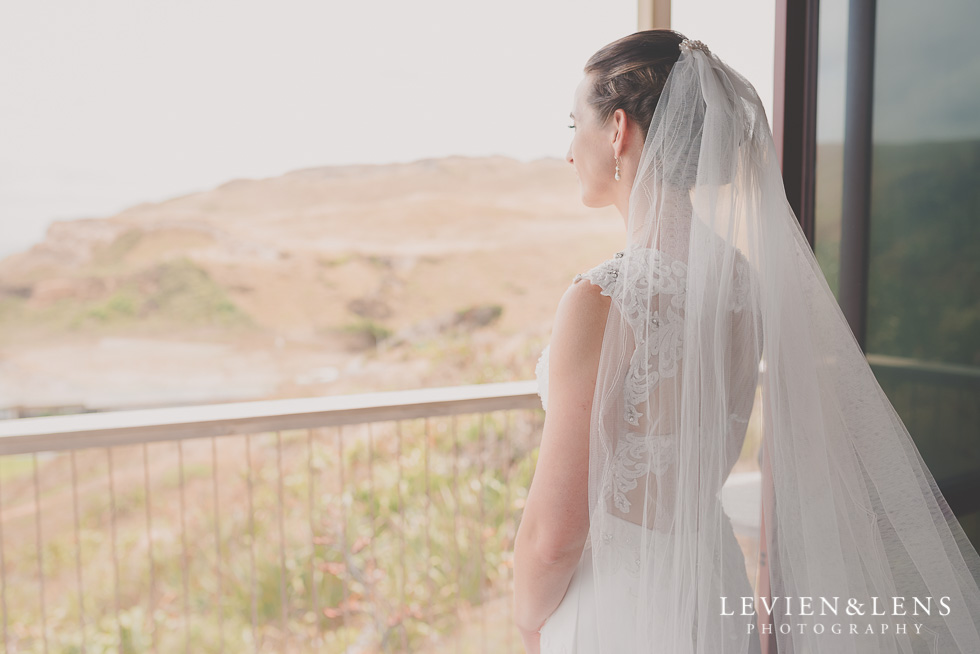 bride look at window Castaways Resort - Kariotahi beach wedding {Auckland lifestyle couples-engagement photographer}