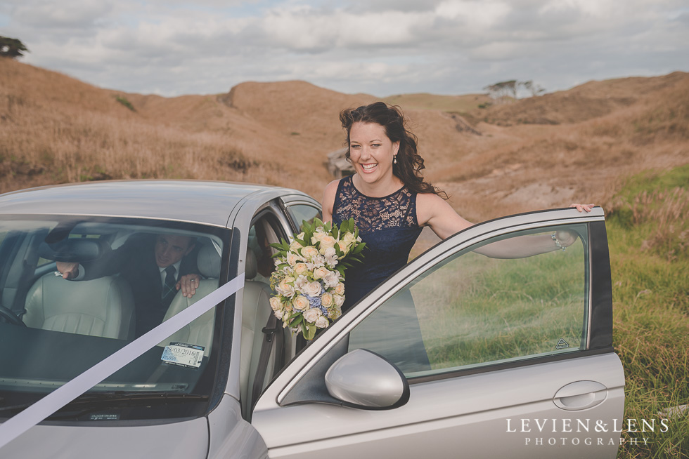 bridesmaid near car bride groom location shoot Kariotahi beach Castaways {Auckland wedding-engagement-couples photographer}