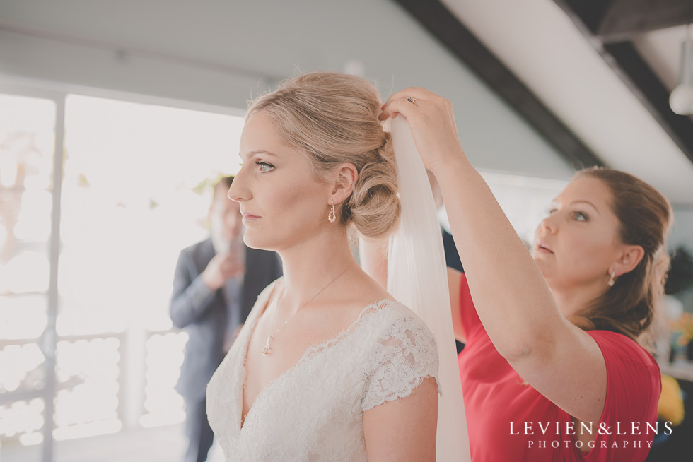 putting veil on bride getting ready Kaurilands Estate {Auckland wedding photographer}