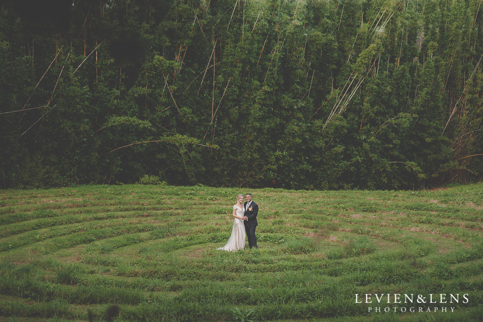 bride and groom intimate session Landscendt Tropical Garden {Auckland lifestyle wedding photographer} on big field in front of forest
