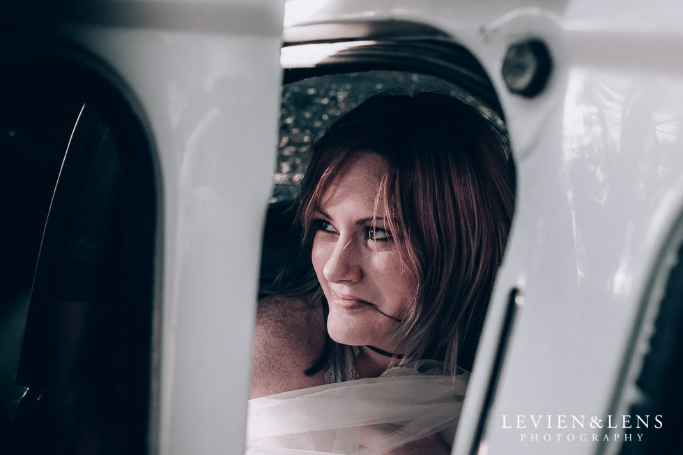 bride looking from the retro car - Cornwall park photo session - winter wedding {Auckland NZ lifestyle weddings photographers}