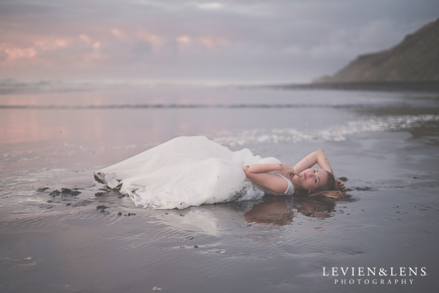 bride portrait laying on beach sunset {Auckland wedding photographer} Castaways Kariotahi