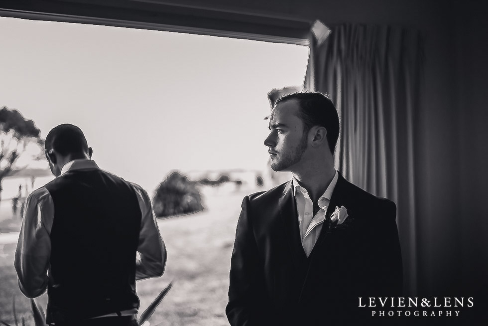 groom getting ready near window - Formosa wedding Golf Resort {Auckland weddings photographer}