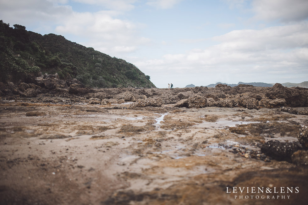 bride and groom walking on rocks - beach cliff - The Duke of Marlborough Hotel - Russel wedding {Northland-New Zealand weddings photographer}