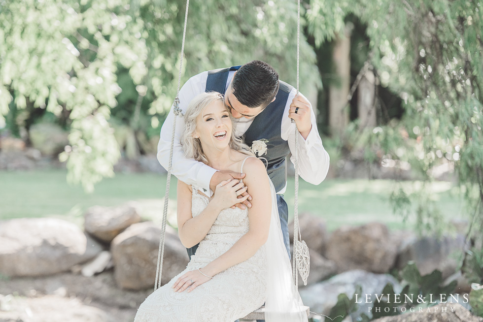 bride with groom on swing- Liddington Gardens - Kerkeri Northland {NZ destination wedding photographer}