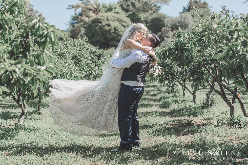 bride and groom kiss in vineyard {Auckland wedding photographer} Liddington gardens