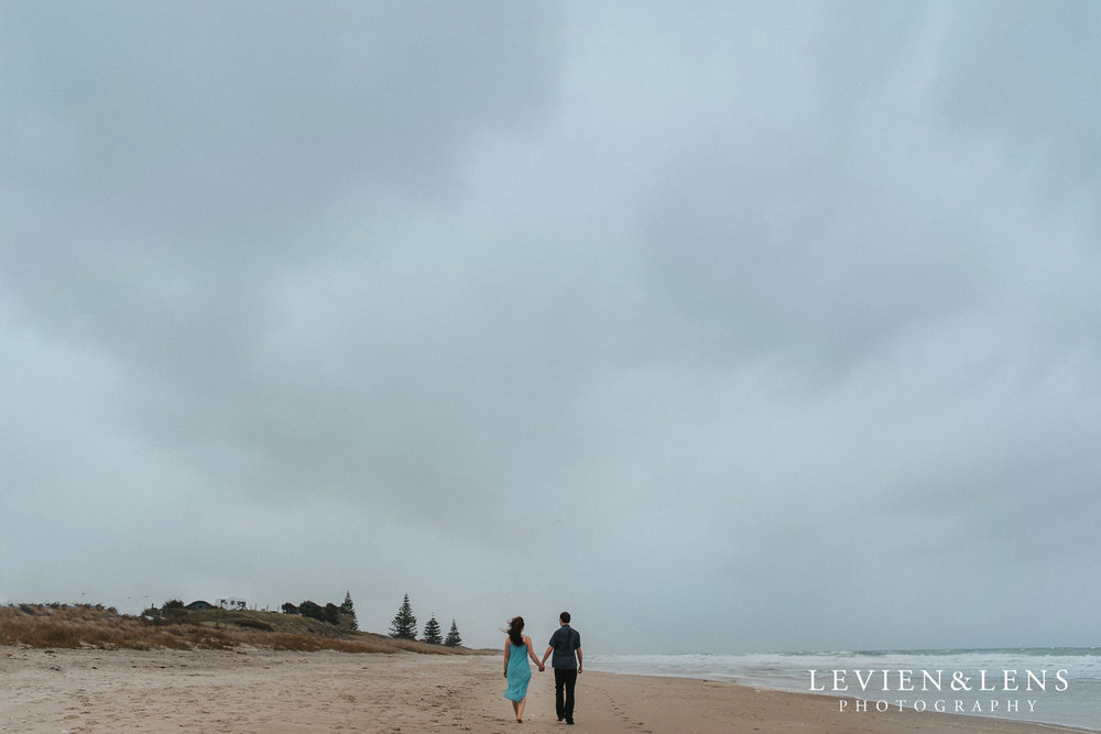 couple walking on Papamoa beach near Mt Maunghanui {Tauranga wedding-engagement photographer}