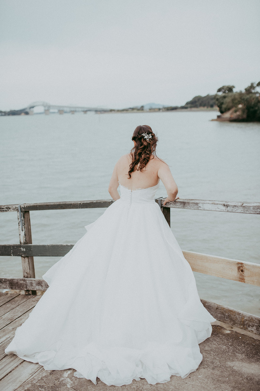 bride at the waterside - view from the back {Auckland top wedding photographers}