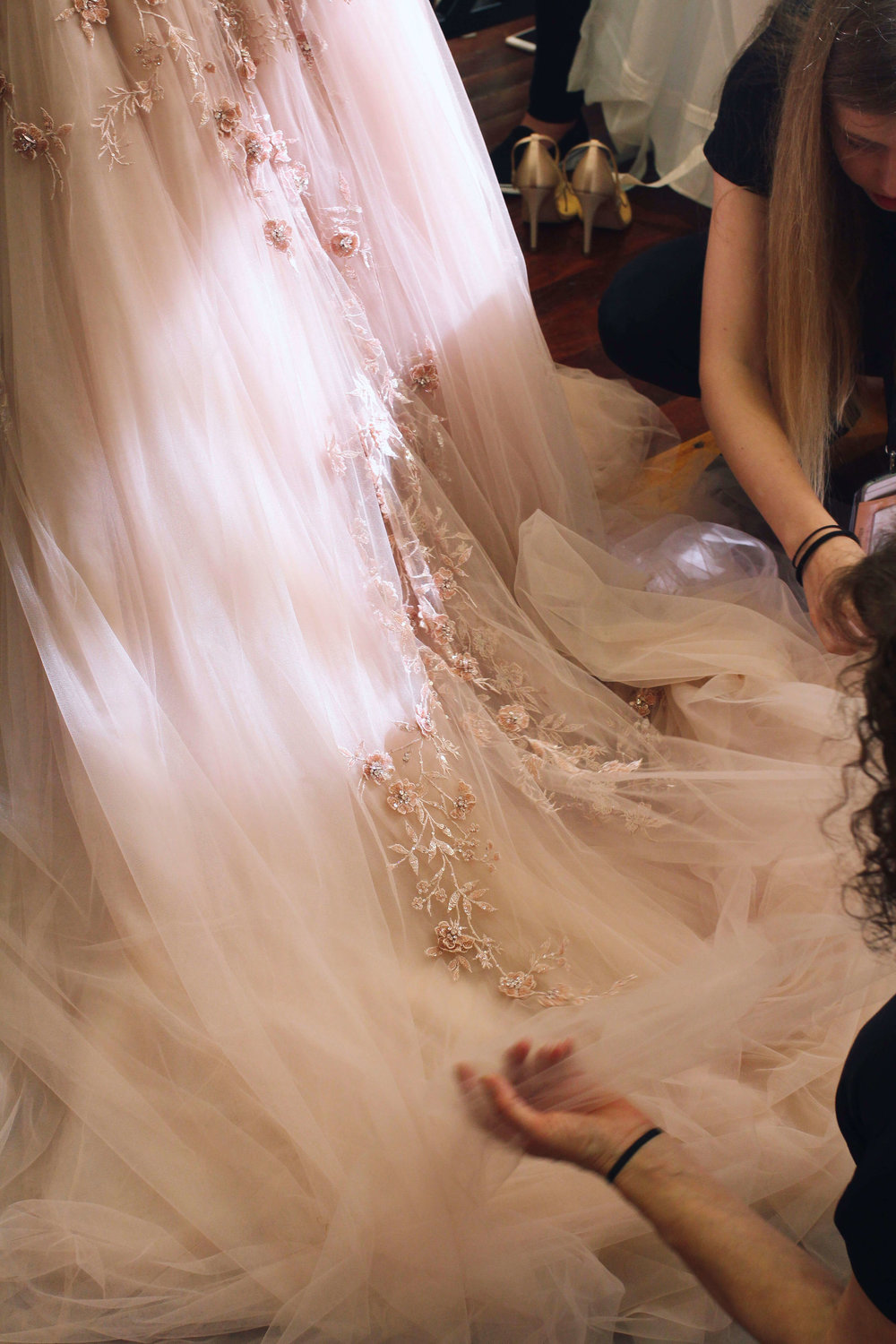 Backstage staff separating each layer of petal pink French tulle before the show.