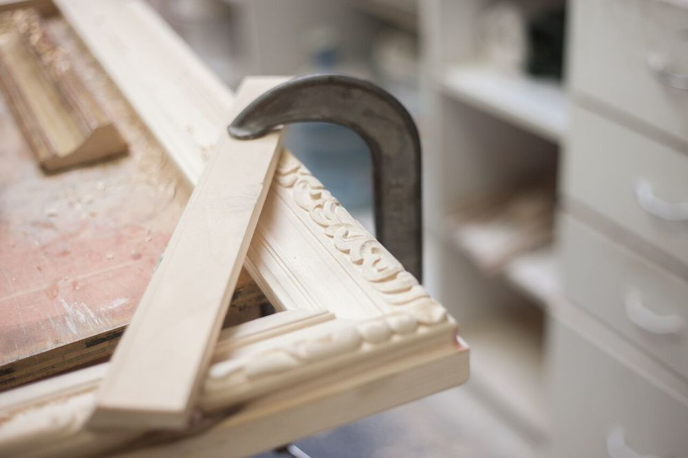 One of the hand-carved frames that takes 6-10 weeks to complete. This frame is clamped on to the table to allow the artisan to hand-carve the most fine details.