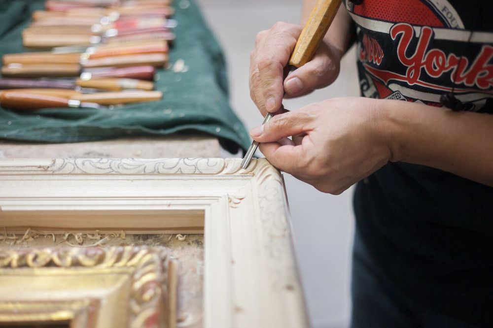 An artisan meticulously carves each detail of this custom frame, using gouaches of all different sizes to create different movements on the ornament of the frame. 150 different gouaches will be used throughout this process to achieve this carving detail.