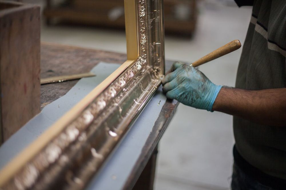 An artisan burnishes the high points of a frame with gold.