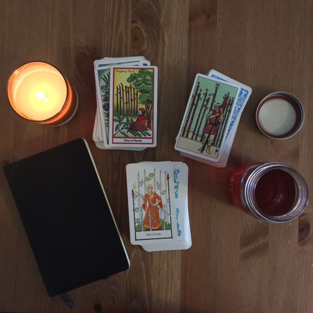 Herbal Tarot on the left, Rider/Waite/Smith on the right, and Tarot of the Old Path on the bottom beside the notebook.  Candle from the shop, and sun tea from this stupid heat wave.