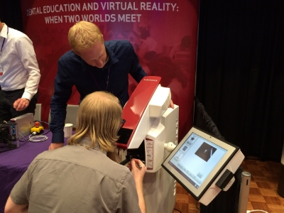 A conference attendee is testing out a dental surgery simulation created by the company Moog. He's looking at a 3-D image of a tooth and holding a drilling tool. The machine convincingly mimics the feeling of the metal sliding across the hard surface of the tooth and the vibration created by drilling.