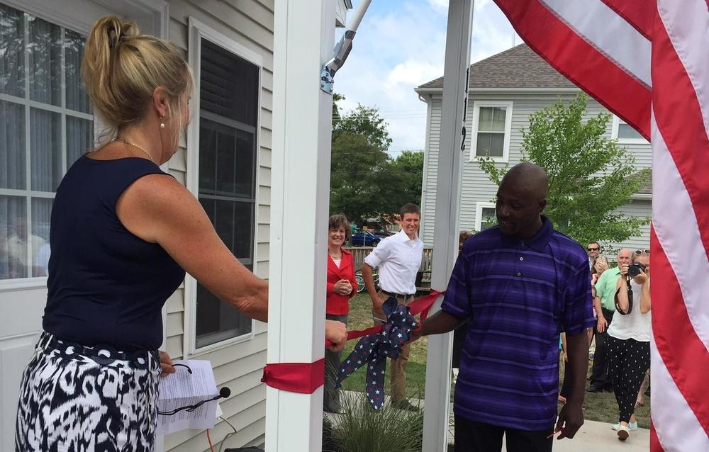 Dolphus cuts the ribbon to celebrate the official opening of our tiny homes. (Photo credits: Chris Bolt  WAER News )