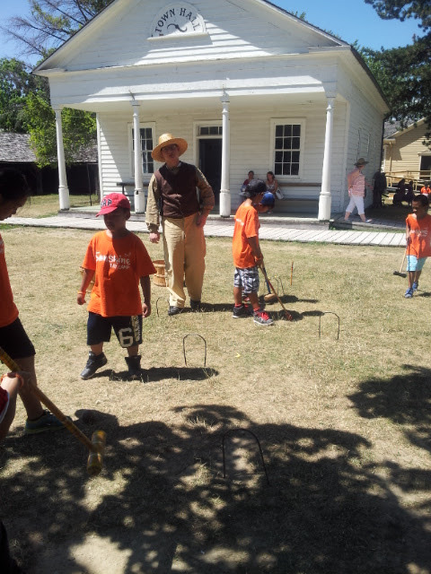 Filipino Pioneers learning how to play (or how not to play) croquet at Black Creek Pioneer Village
