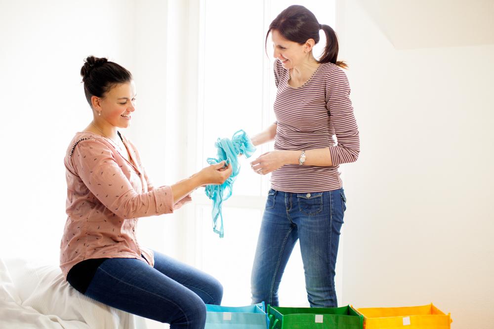 Aufräumaktion Kleiderschrank: Kundin mit Aufräumerin beim Aussortieren von Kleidungsstücken