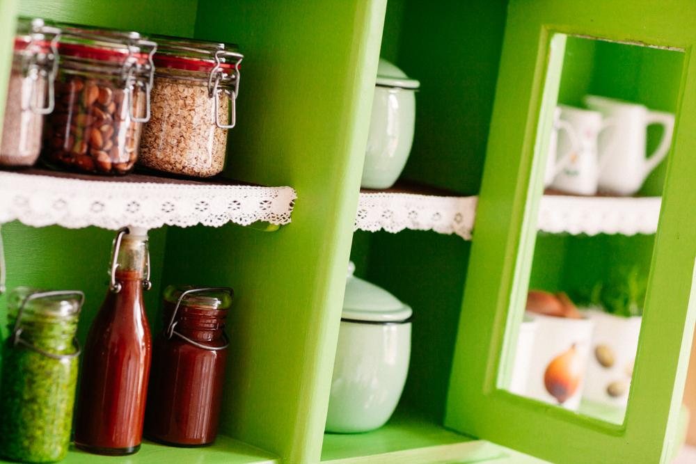 Ordentlich aufgestellte Vorratsgläser und Porzellankännchen in Küchenbuffet