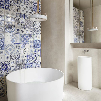 A patchwork of antique Portugese tiles adds drama to the bathroom of a Stockholm home spotted on AD España.