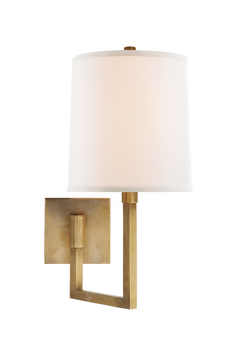 Brass wall sconce with angular arm and white cloth shade.