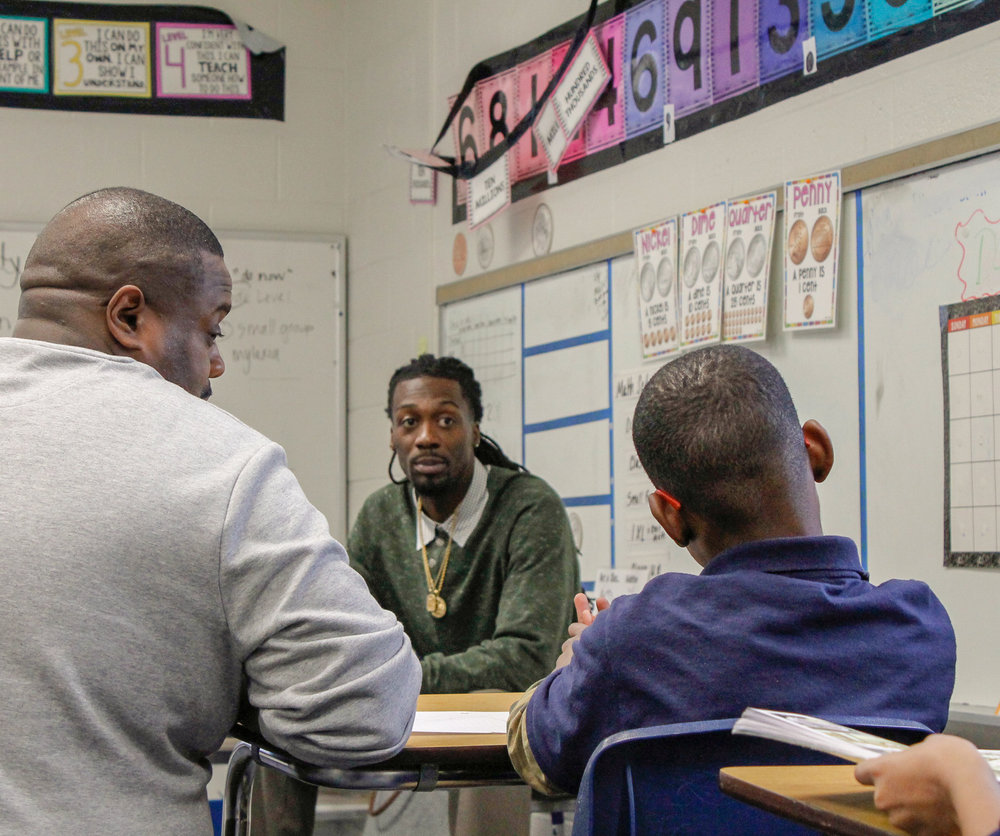 Mr. Alexander and Mr. Neal speak with a student.