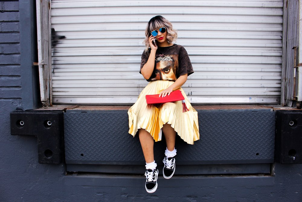 """This outfit was super fun to put together! My goal was to give a edgy but still feminine look. I paired this Tupac distressed graphic tee (Topman $45) with this statement gold pleated skirt (Topshop $20). I love the contrast of pairing a graphic tee with a skirt. I threw on some white laced Bobby socks with my """"old skool"""" Vans ($65). I literally wear these vans with everything guys! They are definately my favorite shoes right now. Then, I finished the look off with a red leather clutch that has tassel detailing on the zipper. P.s. not sure where I got it from...my mom picked it up for me."""