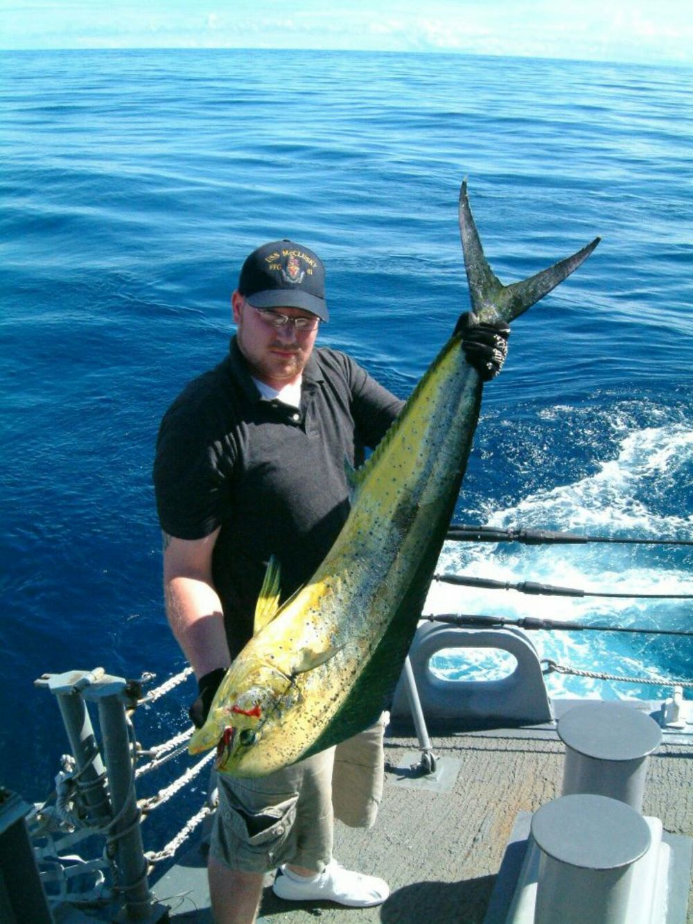 Man in navy catches mahi off of ship 39 s stern into the for Into the blue fishing