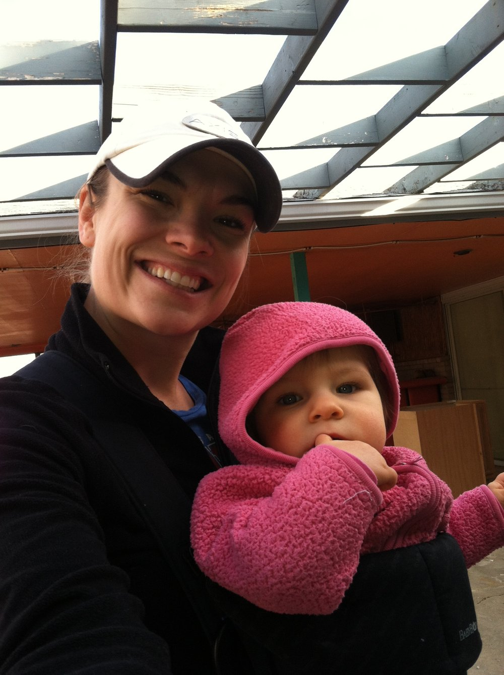 Tia (11 months) and I while project managing our house (also, notice the Tiki bar in the back corner!)