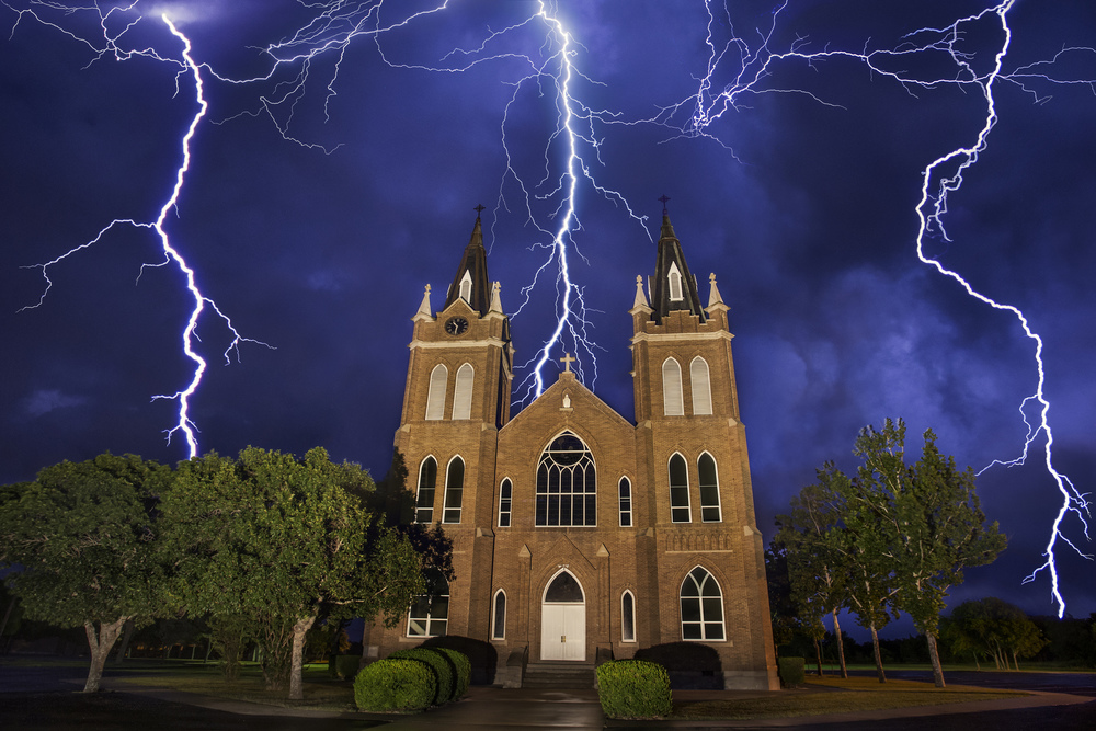 Lightning behind the Holy Trinity Church in Schwertner, Texas Stacked image of 4 photos.