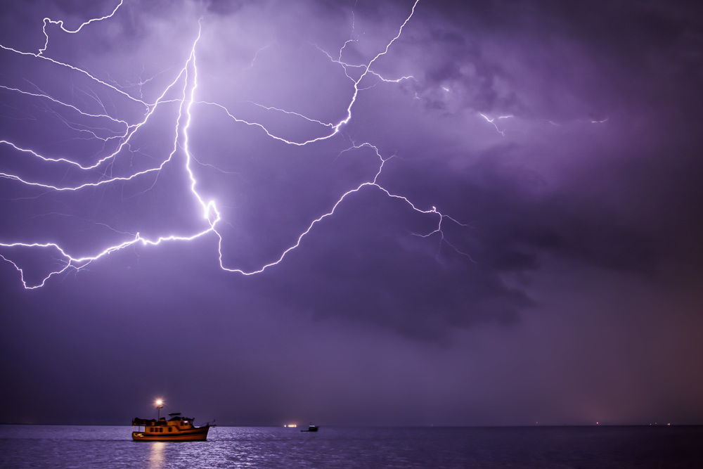 Cloud to cloud lightning over a boat in the Indian River, in Titusville, Florida