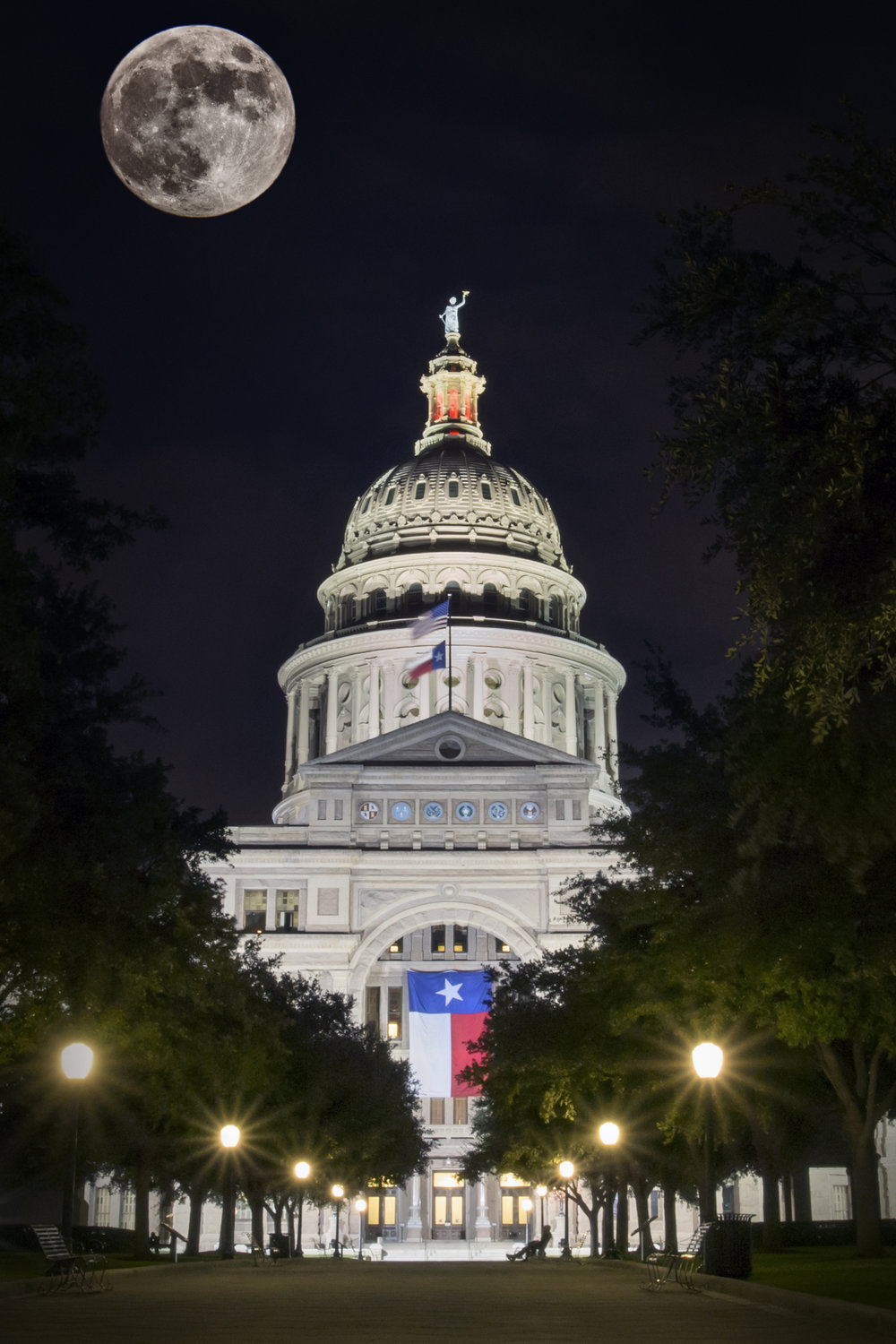 The moon composited into an image of the Texas State Capitol.