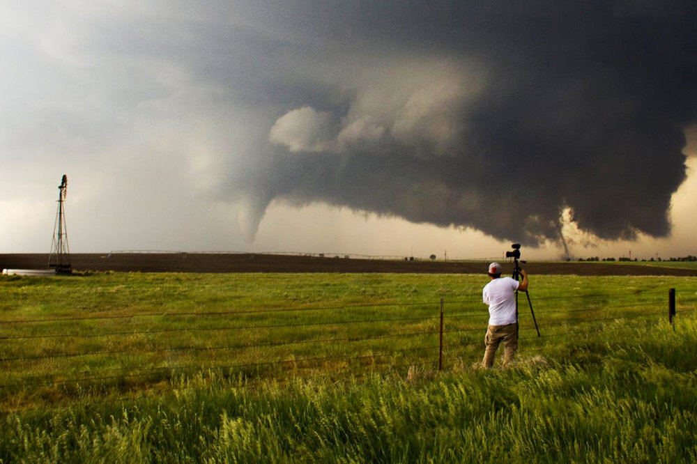 Me setting up my camera as two tornadoes touch down outside of Dodge City, Ks. Image credit Brendon Lindsey.