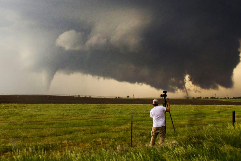 Jason setting up his camera as two tornadoes descend from a supercell near Dodge City, Kansas.