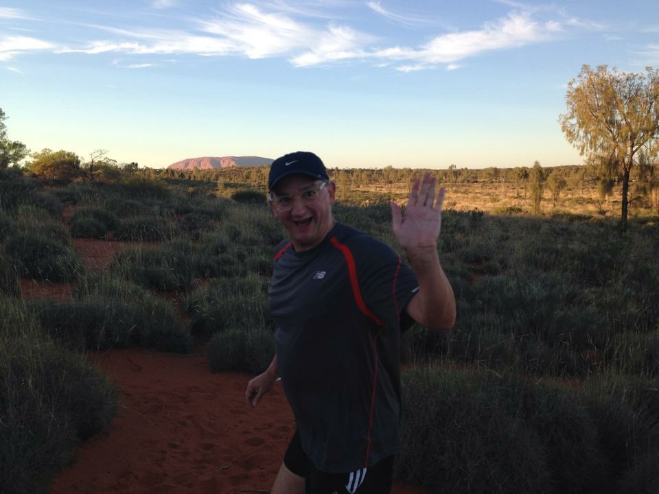 Early morning run through the red dunes with Ayers Rock in the background.