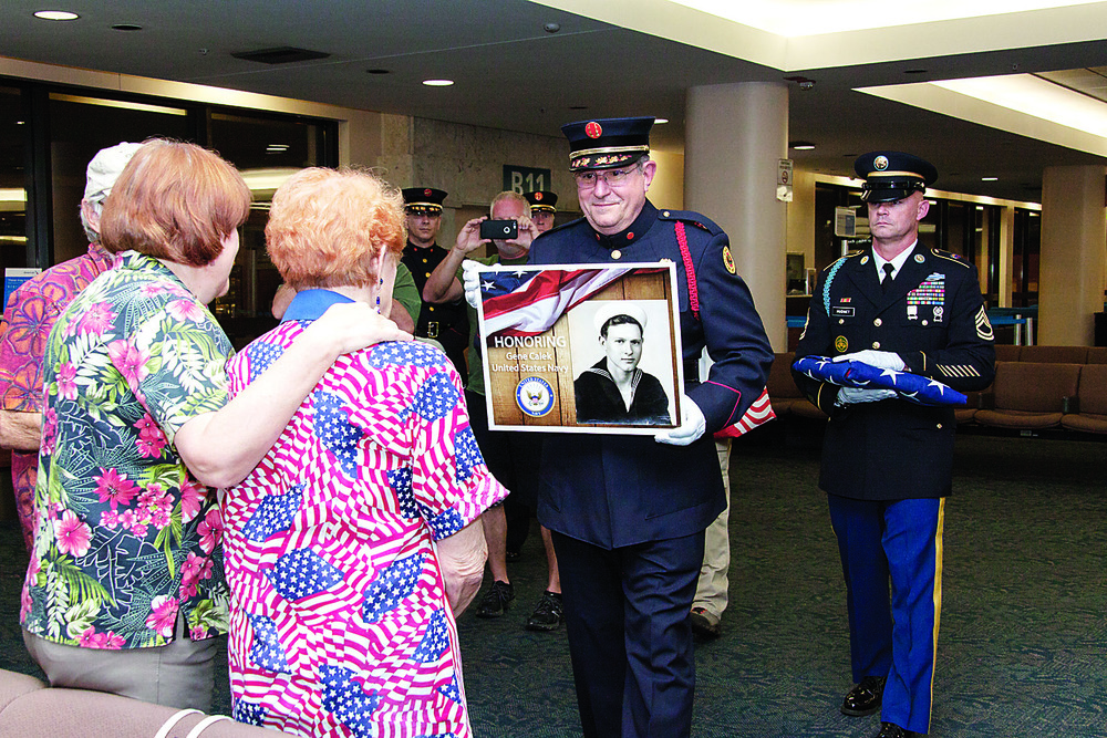 Retired firefighter Rick Gass presents the surviving family of Navy veteran Gene Calek with a photo plaque as Army Sgt. 1st Class Daniel Hudnet follows with a folded flag Oct. 24 on the Southeast Florida Honor Flight.