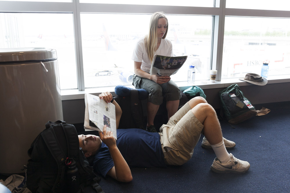 Waiting for our final flight from JFK to Santo Domingo, Dominican Republic, 'Mom' and 'Dad' catch up on the news. We are all pretty exhausted at this point.