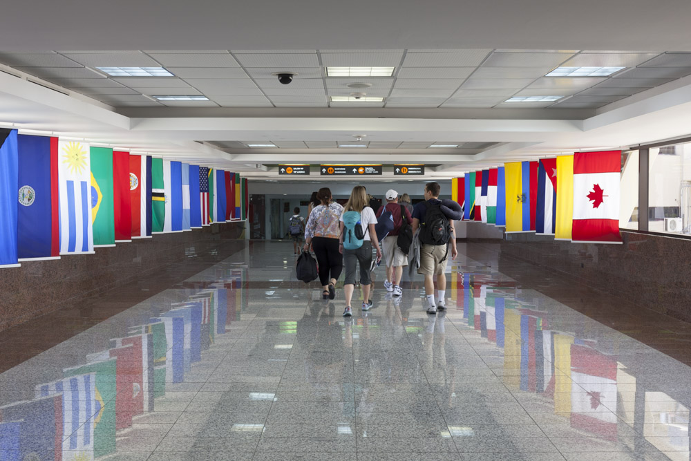 As we exit the plane and head to get our checked luggage, we pass through the hallway of flags.