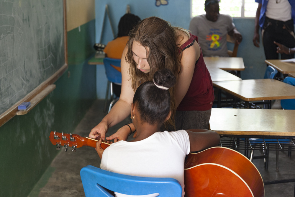Kylie helping a girl with finger placement for a chord.