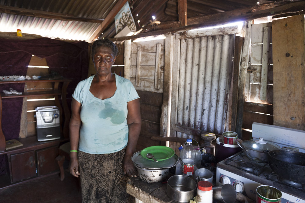A woman stands next to her kitchen in Don Bosco.