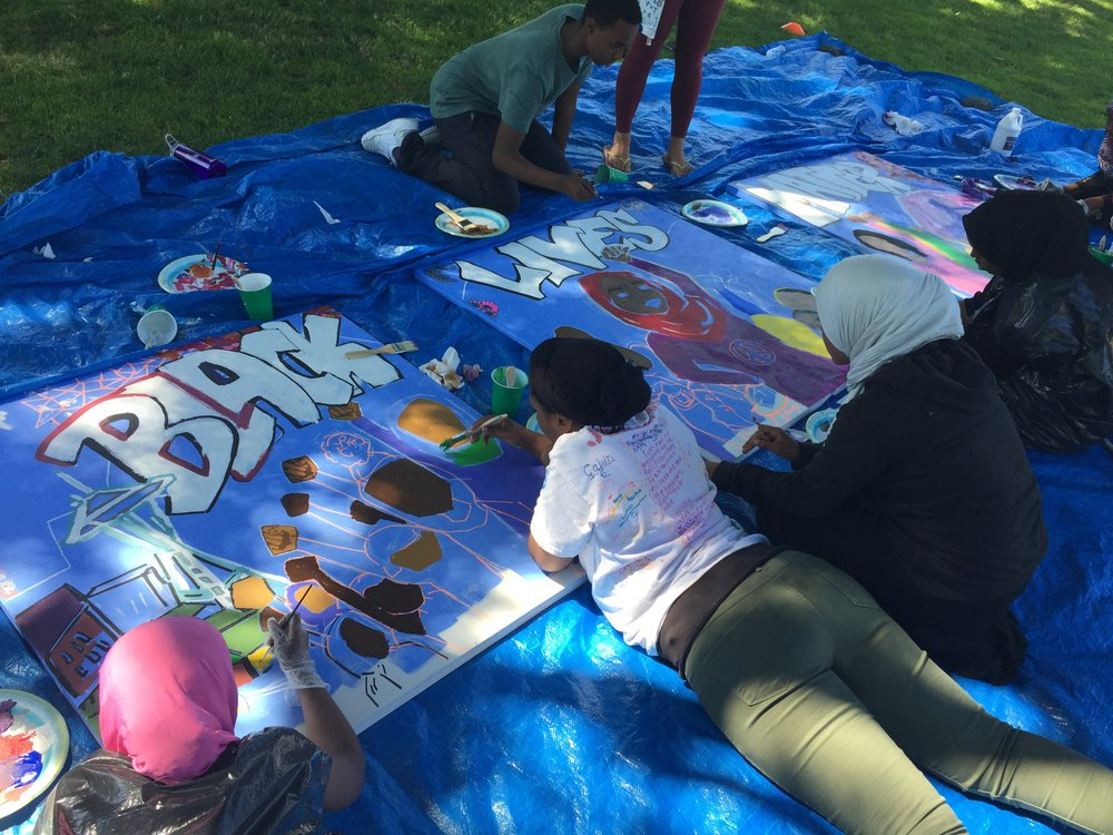 "Summer Mural Project participants paint the mural at the commencement of the program, featuring the youth-decided design and message stating ""Black Lives Matter"""