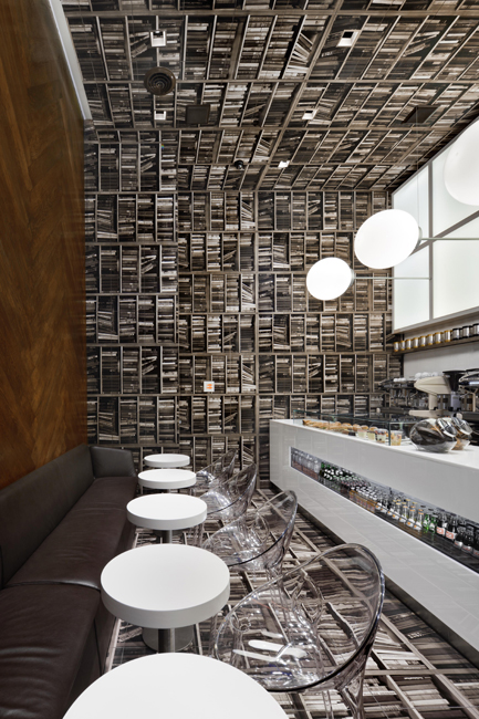 "ncarrot2 :           The architects at Nemo Workshop designed this new espresso bar in New York City called D'espresso. The interior looks like the room has been tilted on its side:     The ""books"" are actually tiles printed with sepia-toned photos of bookshelves at a local travel bookstore that ring the room, including the floor, walls and ceiling. In addition to painting unusual surfaces with intriguing patterns — whoa, you're standing on books! — it gives an Alice in Wonderland-esque sense that the room has been suddenly upended."