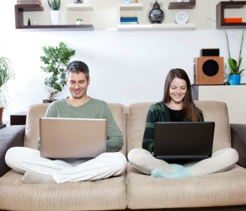 Happy young couple smiling and using laptops