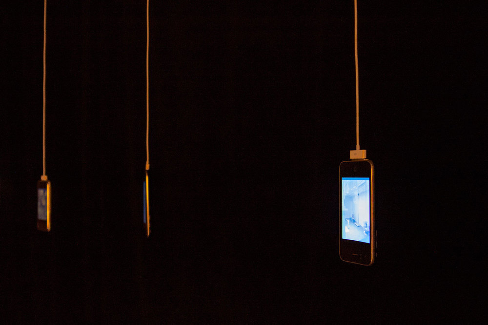 iPhones are freely hanging by their charging cables.